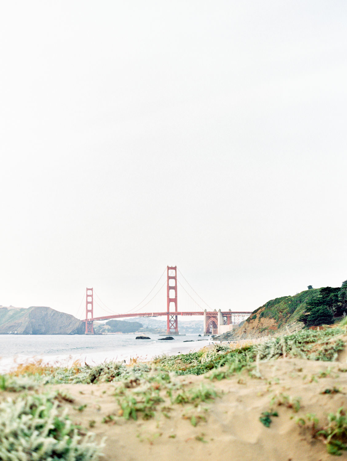 View of Golden Gate Bridge. Baker Beach Engagement Session in San Francisco captured on film by Cavin Elizabeth