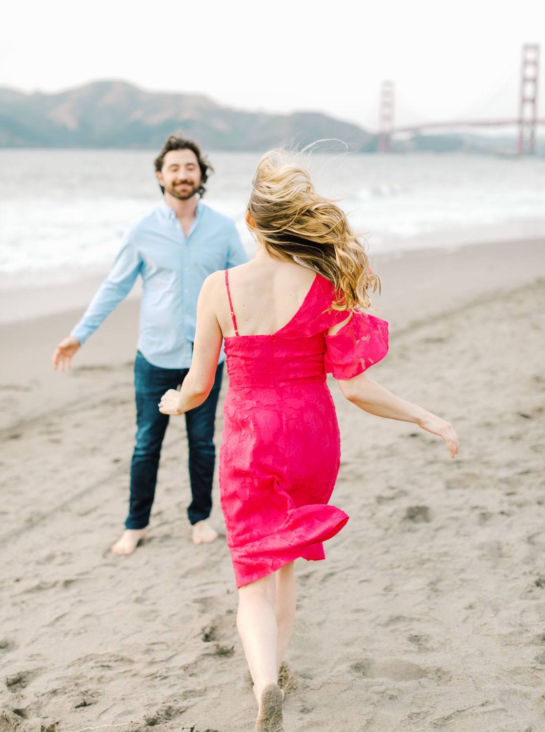 Bride in fuschia pink dress and groom in light blue button down and jeans. Baker Beach Engagement Session in San Francisco by Cavin Elizabeth