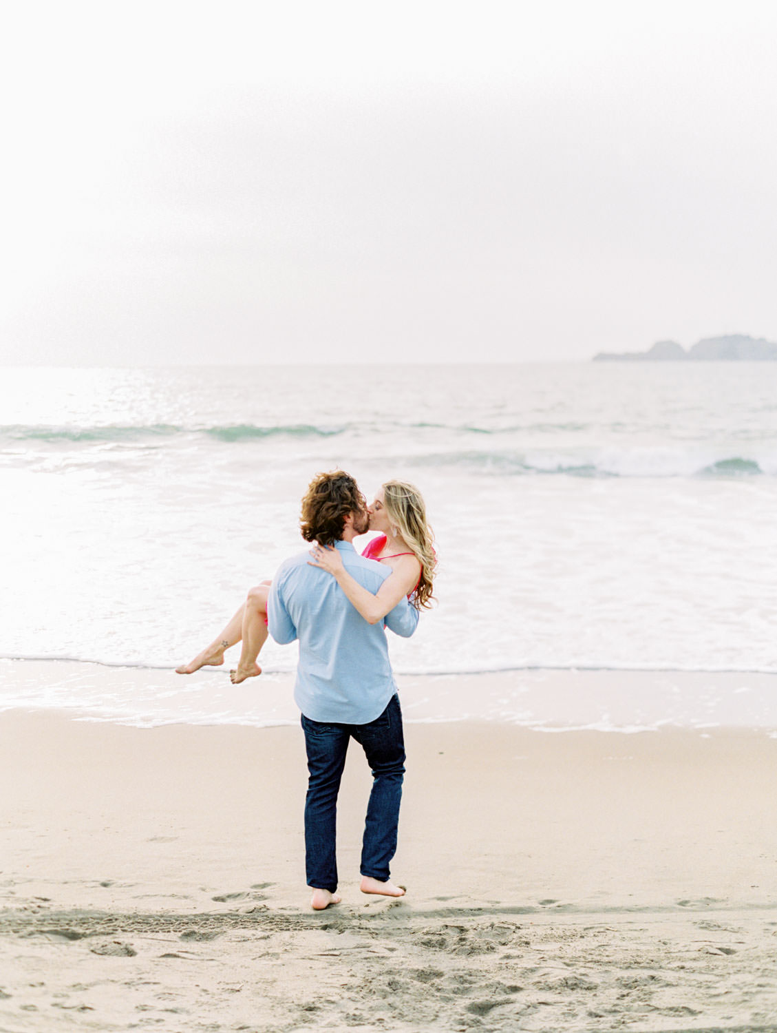 Groom carrying bride to the water, Baker Beach Engagement Session in San Francisco captured on film by Cavin Elizabeth