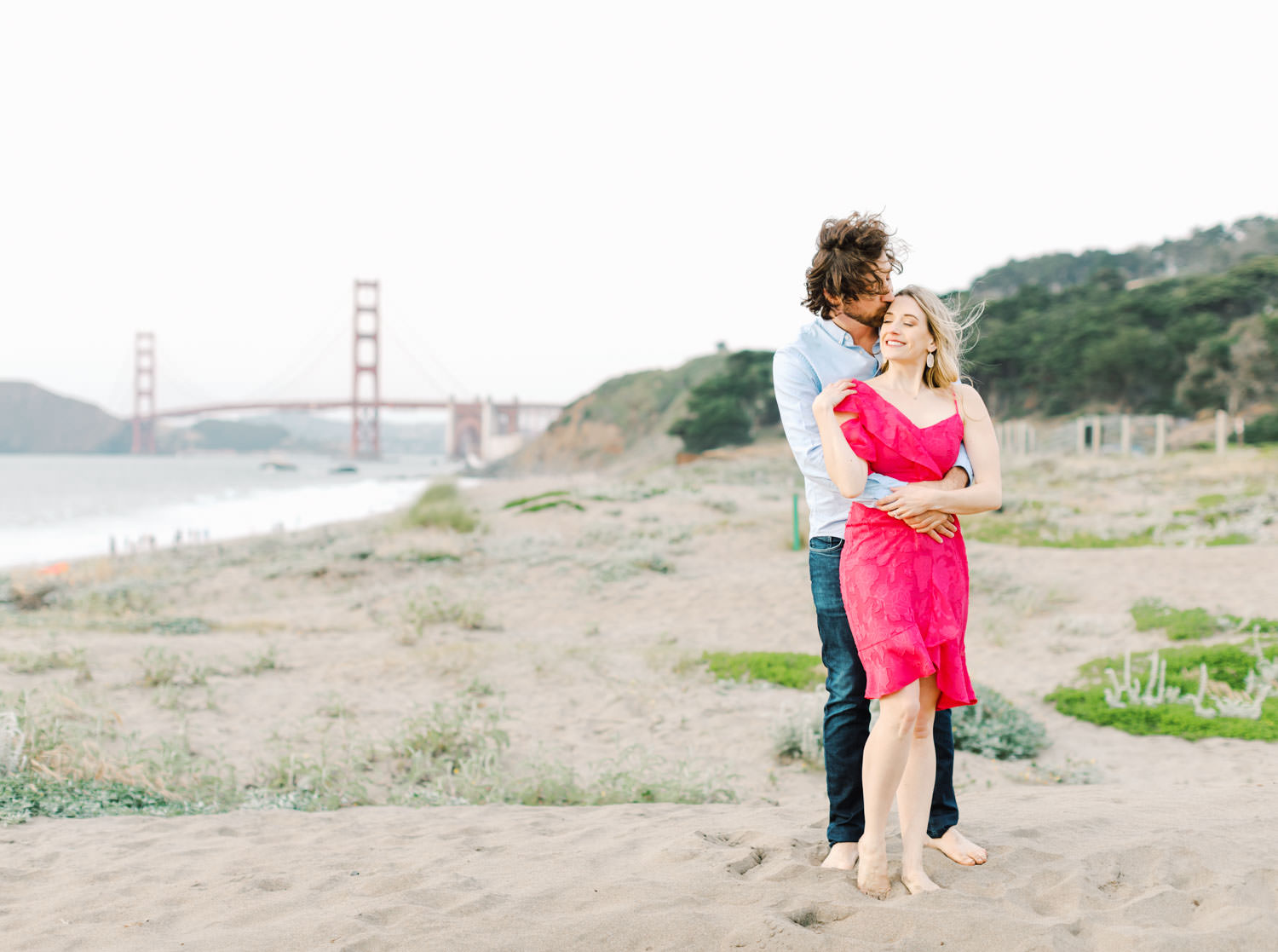 View of Golden Gate Bridge with Bride in fuschia pink dress and groom in light blue button down and jeans. Baker Beach Engagement Session in San Francisco by Cavin Elizabeth