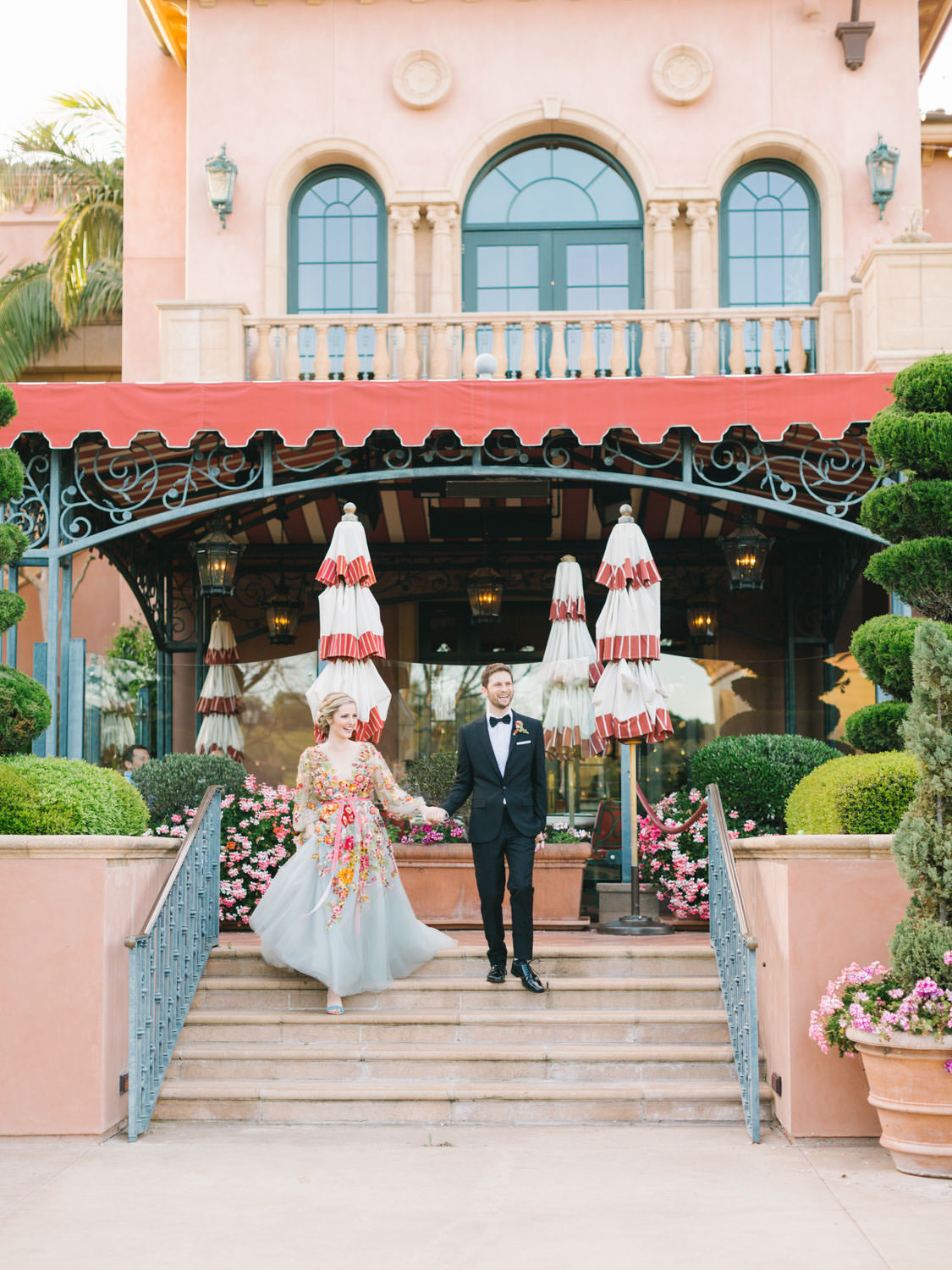 Bride and groom grand entrance into reception. Bride wearing colorful Marchesa wedding gown with blue, pink, yellow, green, and orange floral appliques. A Wedding Photographer's Fairmont Grand Del Mar Wedding