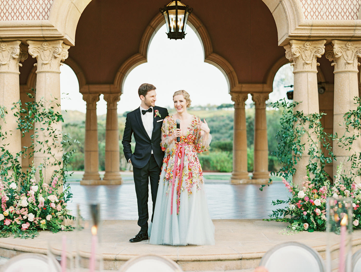 Bride and groom speech on a stage with columns covered in climbing smilax with arrangement at the bottom consisting of roses, ranunculus, daffodils, peonies, and sweet peas. Bride wearing colorful Marchesa wedding gown with blue, pink, yellow, green, and orange floral appliques. A Wedding Photographer's Fairmont Grand Del Mar Wedding