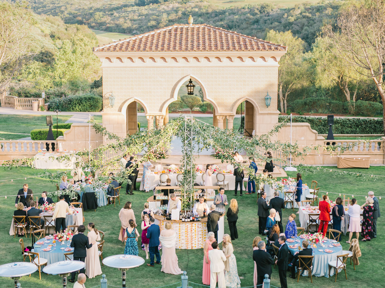 Al fresco reception with round and long tables covered in blue and neutral velvet linen with crossback chairs. Round circular bar with wagon wheel market lighting covered in greenery smilax. A Wedding Photographer's Fairmont Grand Del Mar Wedding