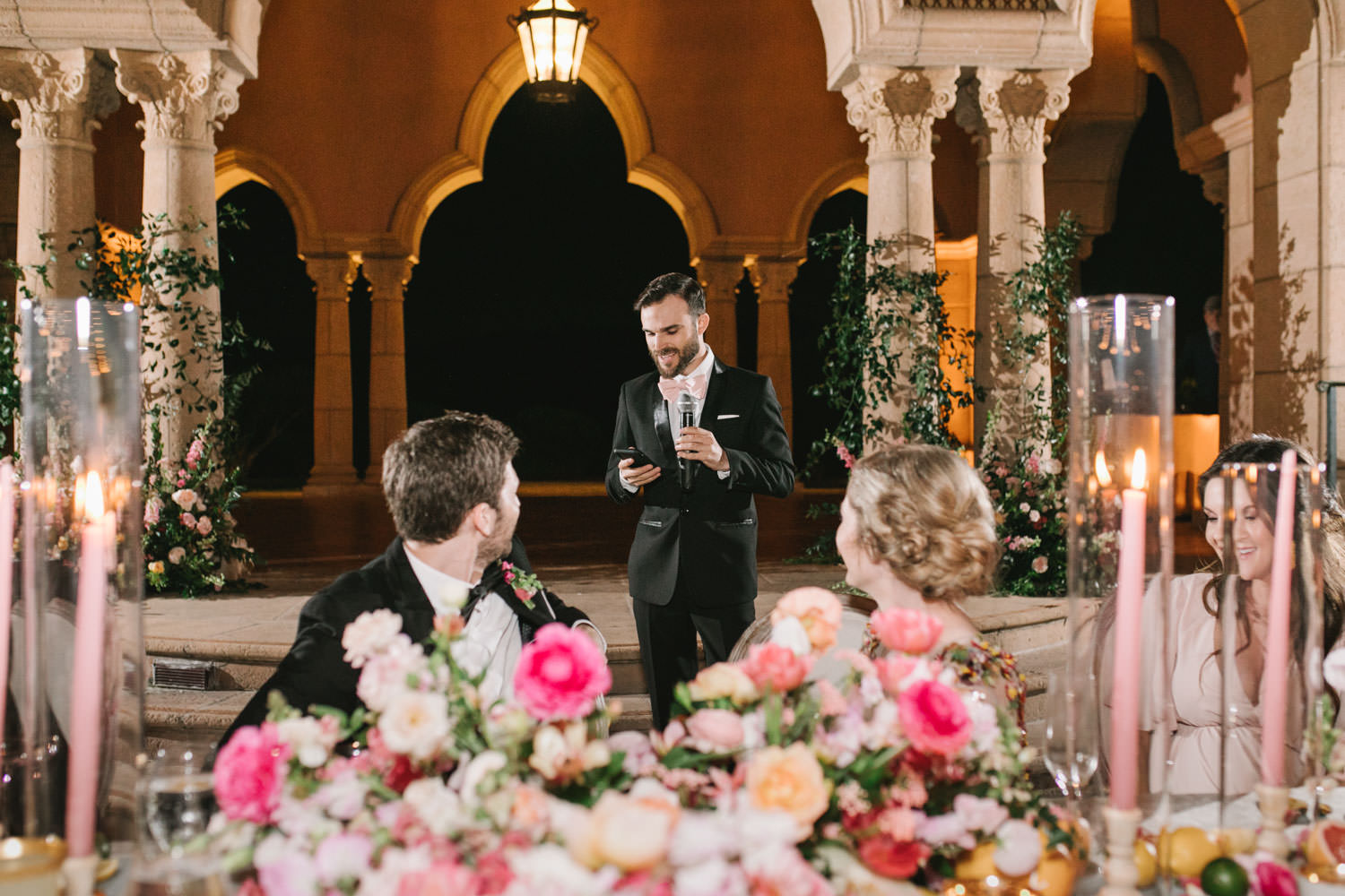 Bridesman toast on a stage with columns covered in climbing smilax with arrangement at the bottom consisting of roses, ranunculus, daffodils, peonies, and sweet peas. A Wedding Photographer's Fairmont Grand Del Mar Wedding