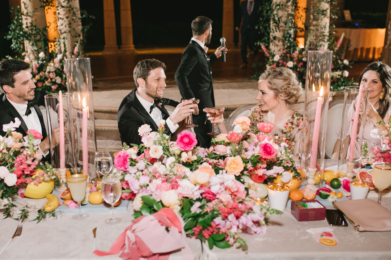 Best man toast on a stage with columns covered in climbing smilax with arrangement at the bottom consisting of roses, ranunculus, daffodils, peonies, and sweet peas. A Wedding Photographer's Fairmont Grand Del Mar Wedding