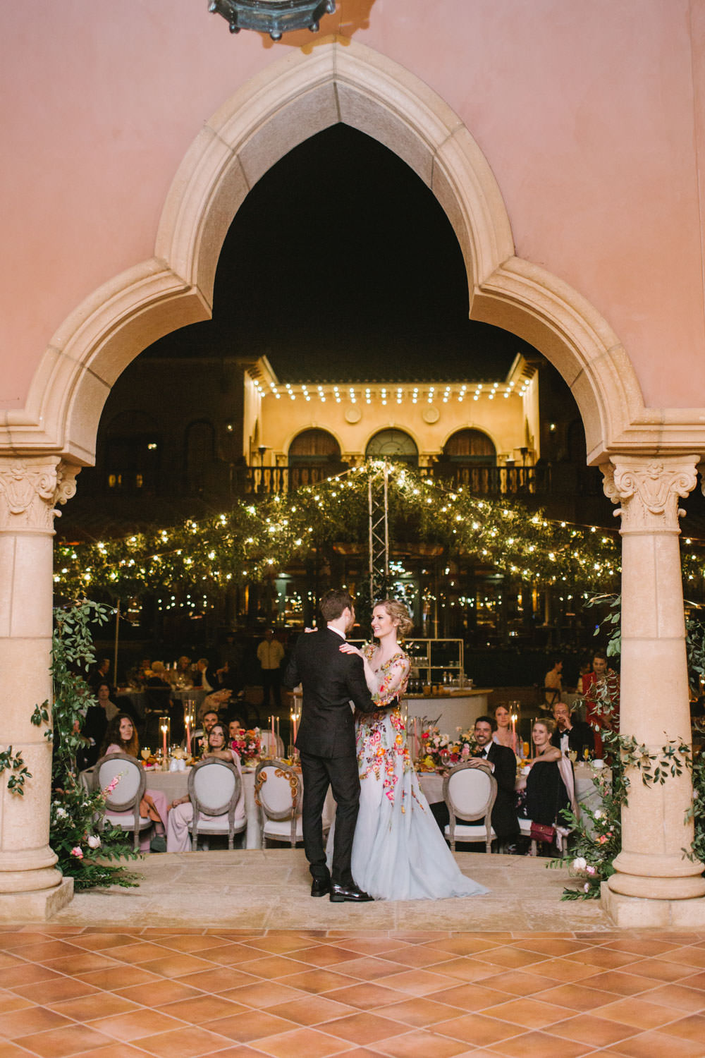 Bride and groom first dance on a stage with with wagon wheel market lights covered in greenery in the background. Bride wearing colorful Marchesa wedding gown with blue, pink, yellow, green, and orange floral appliques. A Wedding Photographer's Fairmont Grand Del Mar Wedding
