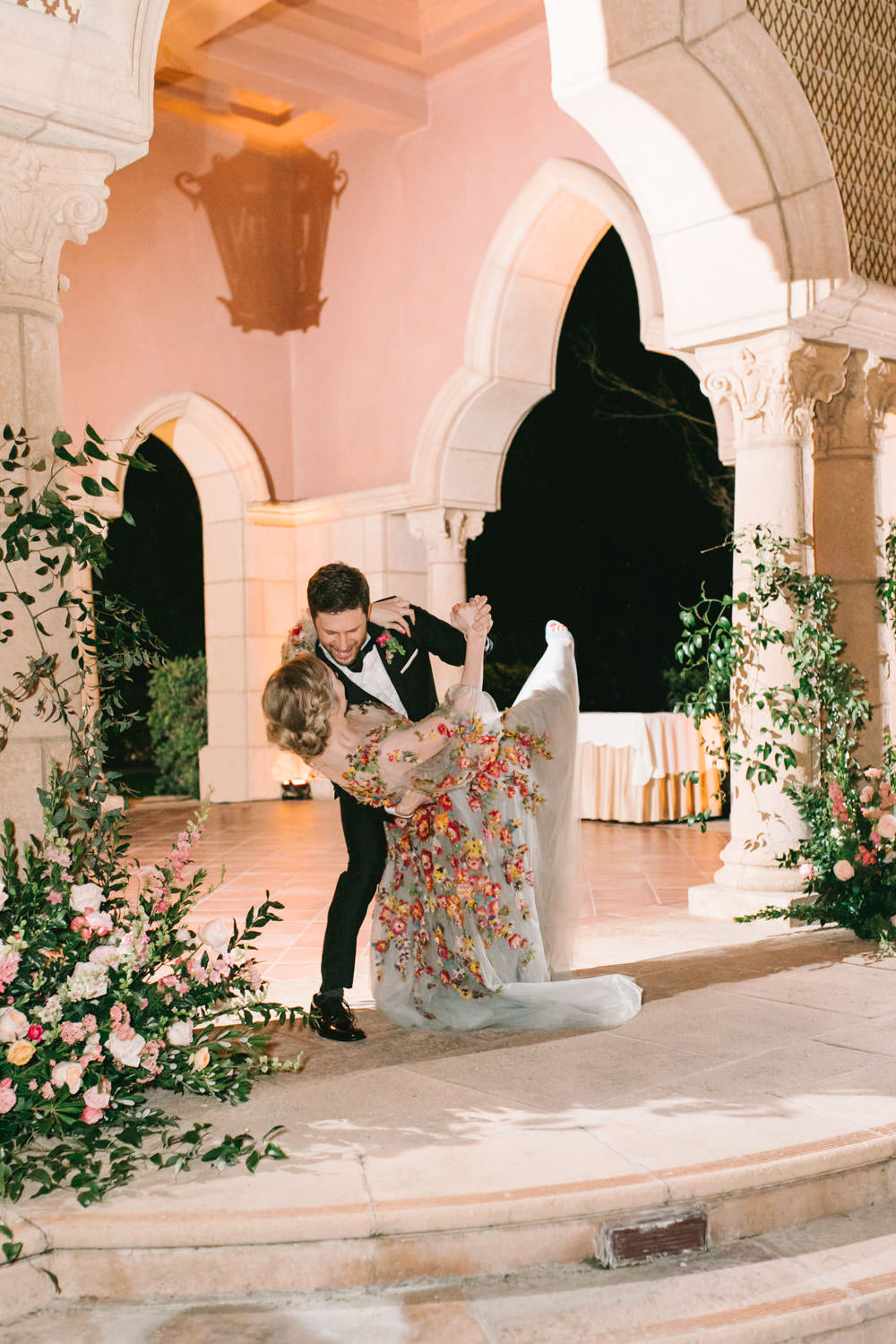 Bride and groom first dance on a stage with columns covered in climbing smilax with arrangement at the bottom consisting of roses, ranunculus, daffodils, peonies, and sweet peas. Bride wearing colorful Marchesa wedding gown with blue, pink, yellow, green, and orange floral appliques. A Wedding Photographer's Fairmont Grand Del Mar Wedding
