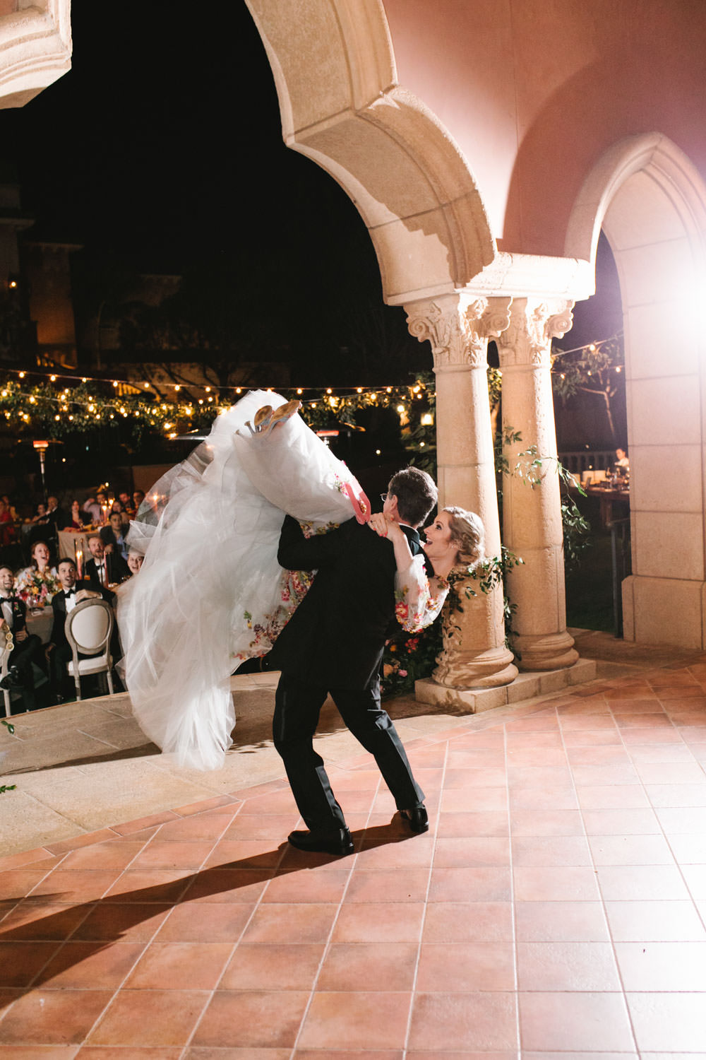 Father daughter dance on a stage with with wagon wheel market lights covered in greenery in the background. Bride wearing colorful Marchesa wedding gown with blue, pink, yellow, green, and orange floral appliques. A Wedding Photographer's Fairmont Grand Del Mar Wedding