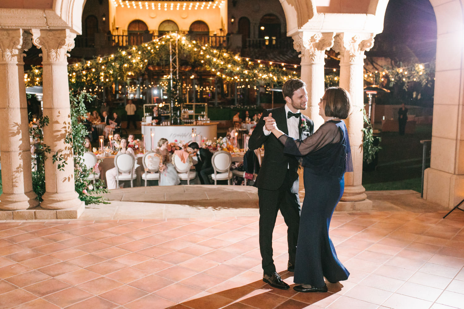Mother son dance on a stage with with wagon wheel market lights covered in greenery in the background. A Wedding Photographer's Fairmont Grand Del Mar Wedding