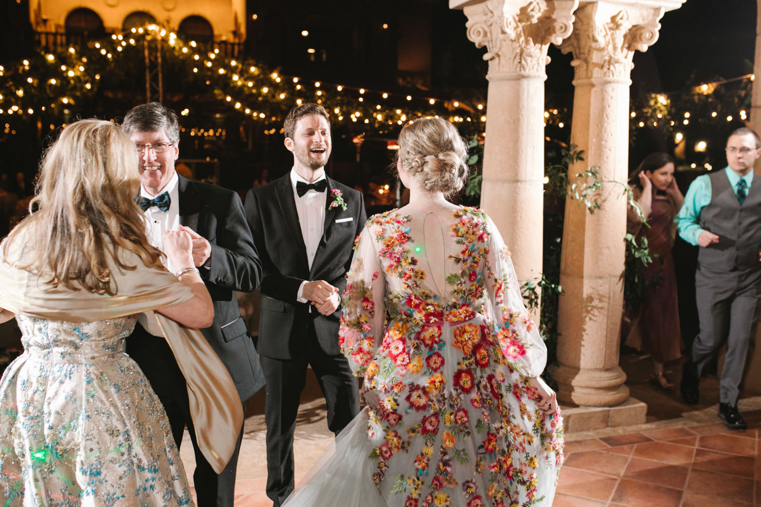 Bride and groom dance on a stage with with wagon wheel market lights covered in greenery in the background. Bride wearing colorful Marchesa wedding gown with blue, pink, yellow, green, and orange floral appliques. A Wedding Photographer's Fairmont Grand Del Mar Wedding