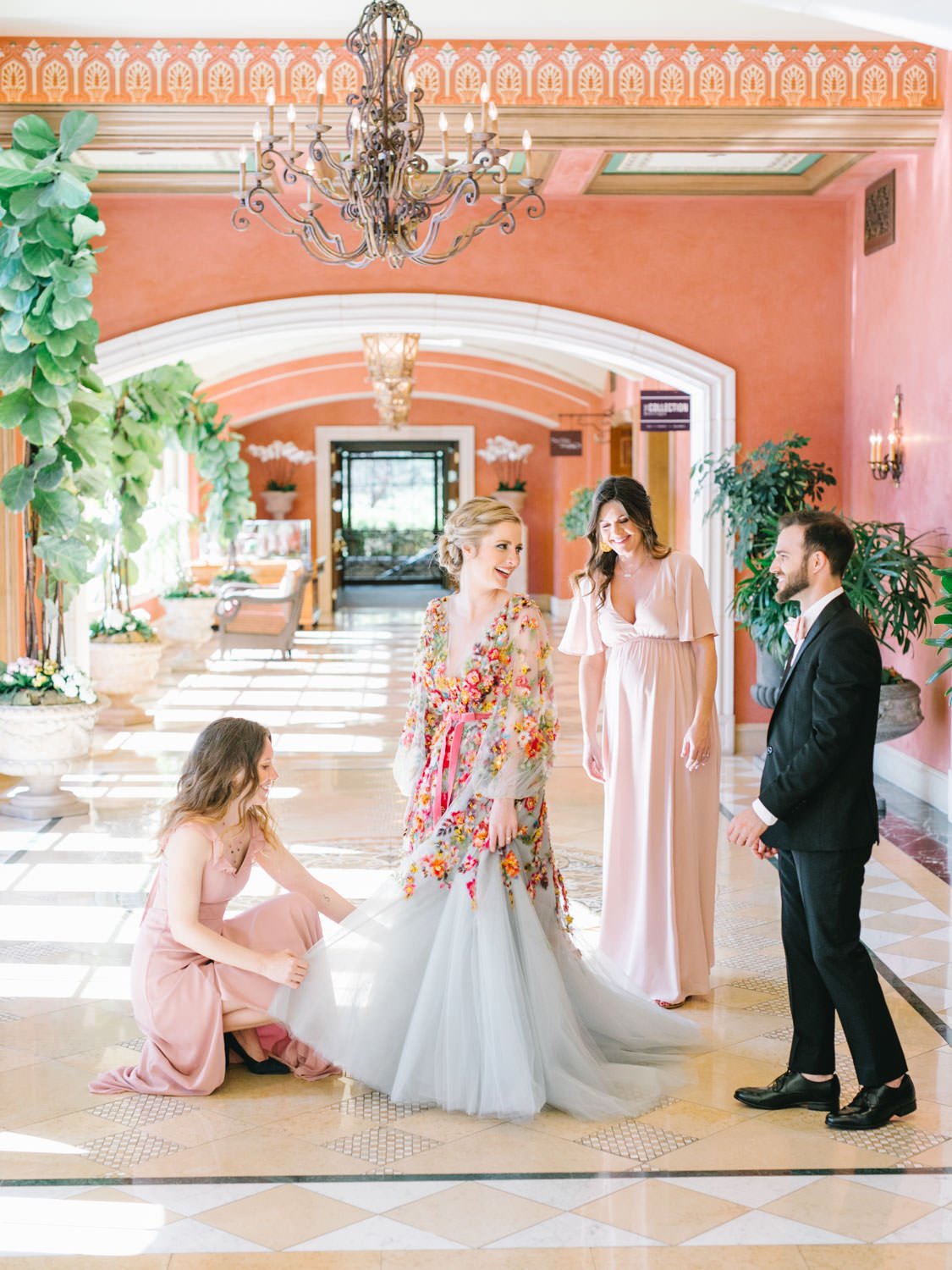 Bridesmaids and bridesman helping bride into her Marchesa blue and pink floral long sleeve couture gown with floral appliques. Fairmont Grand del Mar wedding published on Martha Stewart Weddings