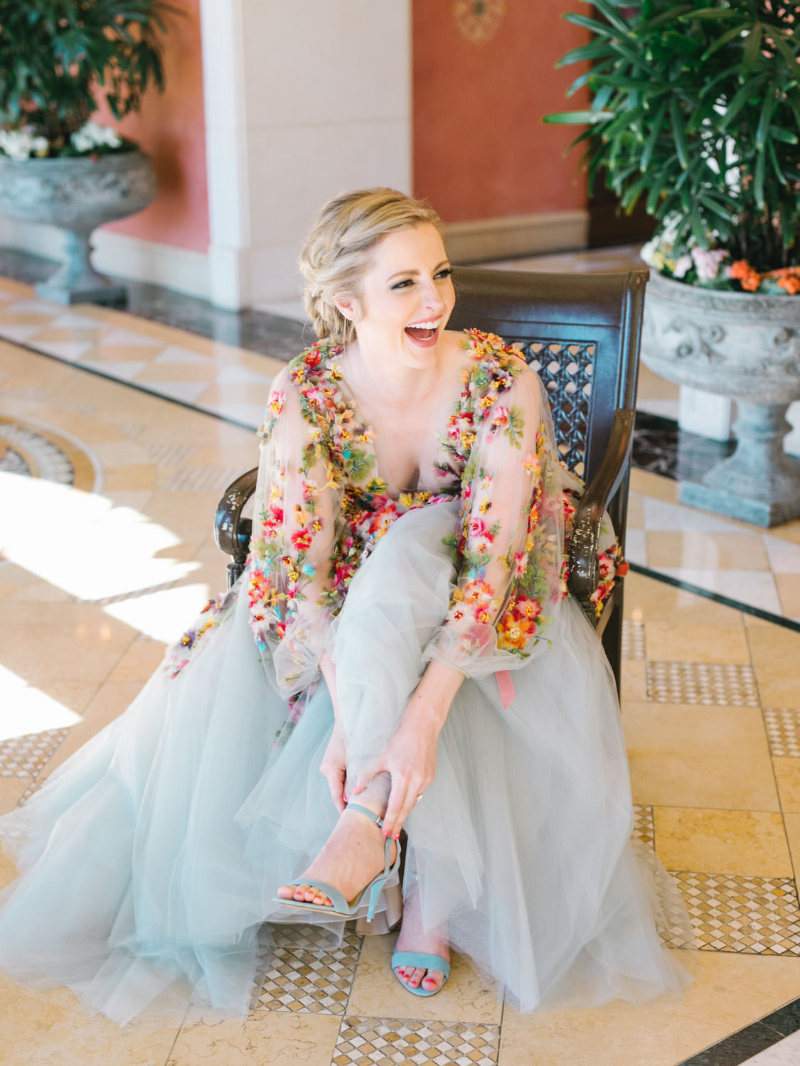 Bride putting on velvet blue sandal heels wearing a Marchesa blue and pink floral long sleeve couture gown with floral appliques. Fairmont Grand del Mar wedding published on Martha Stewart Weddings