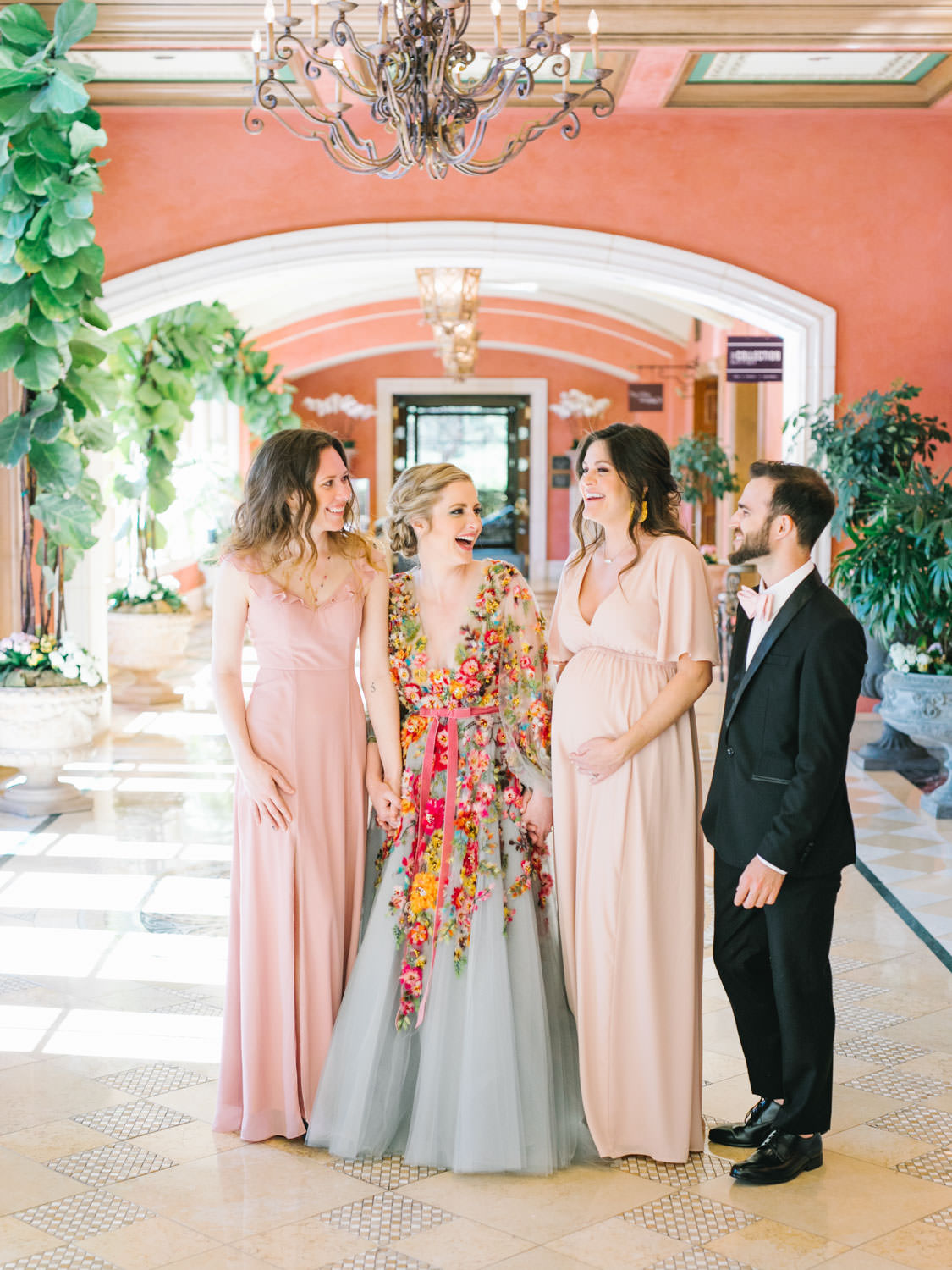 Bridesmaids in mix match mauve and blush dresses and bridesman in in black tux with mauve bowtie with Bride wearing a Marchesa blue and pink floral long sleeve couture gown with floral appliques. Fairmont Grand del Mar wedding published on Martha Stewart Weddings