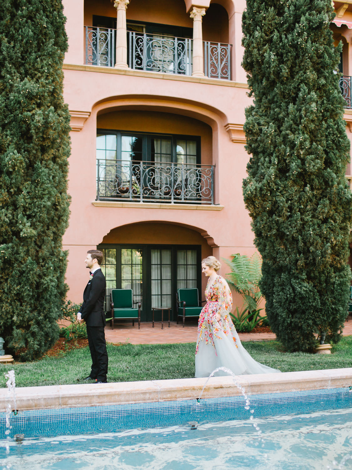 Groom in a black tux waiting during first look for Bride wearing a Marchesa blue and pink floral long sleeve couture gown with floral appliques. Fairmont Grand del Mar wedding published on Martha Stewart Weddings