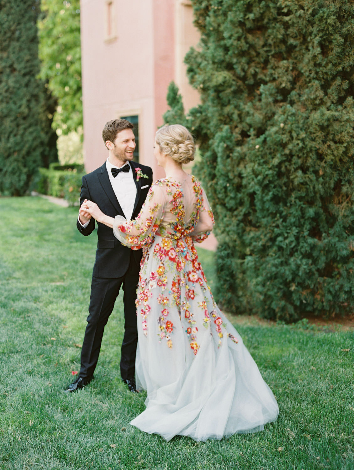 Groom in a black tux smiling during first look at Bride wearing a Marchesa blue and pink floral long sleeve couture gown with floral appliques. Fairmont Grand del Mar wedding published on Martha Stewart Weddings
