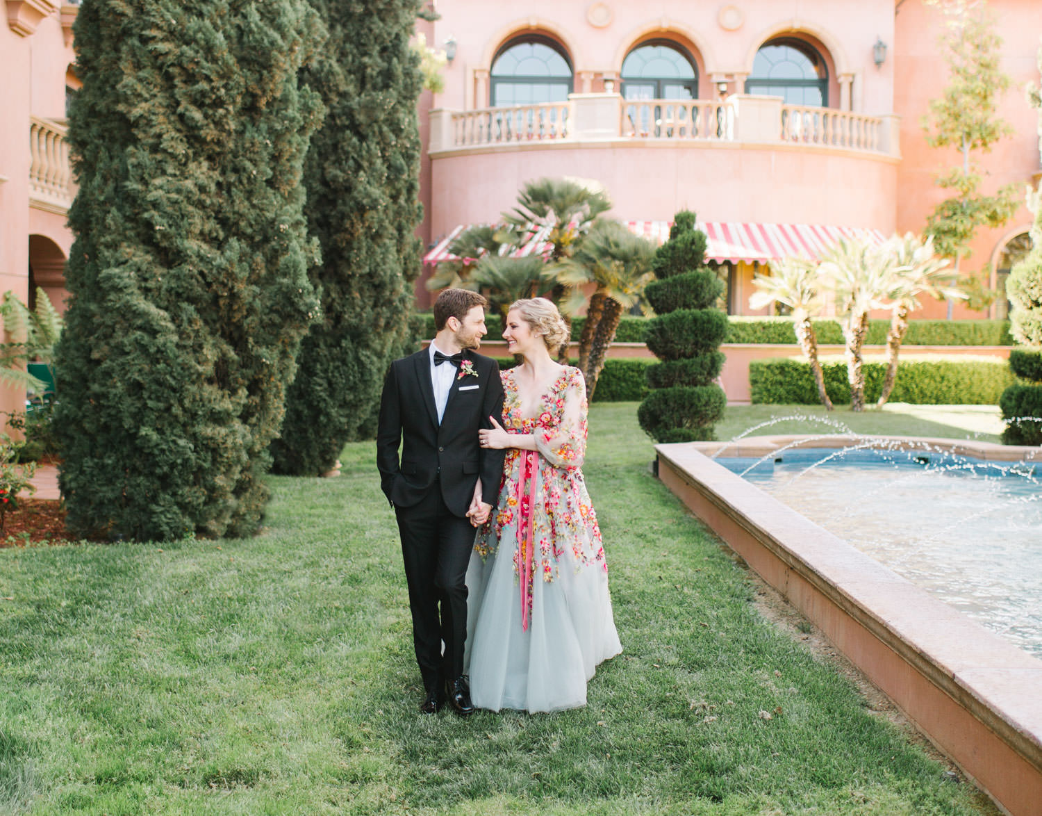 Groom in a black tux walking with bride wearing a colorful Marchesa blue and pink floral long sleeve couture gown with floral appliques. Fairmont Grand del Mar wedding published on Martha Stewart Weddings