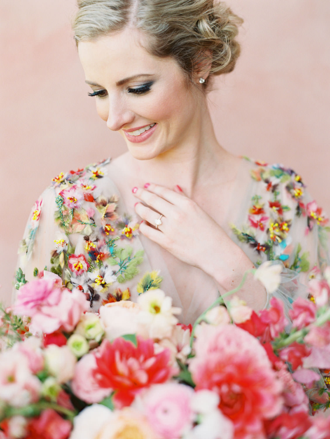 Bride with bold eyemakeup wearing a Marchesa blue and pink floral long sleeve couture gown with floral appliques. Large bridal bouquet of mostly pink tones roses, peonies, ranunculus, and sweet peas with long bright pink and blush and mauve silk ribbons. Fairmont Grand del Mar wedding published on Martha Stewart Weddings