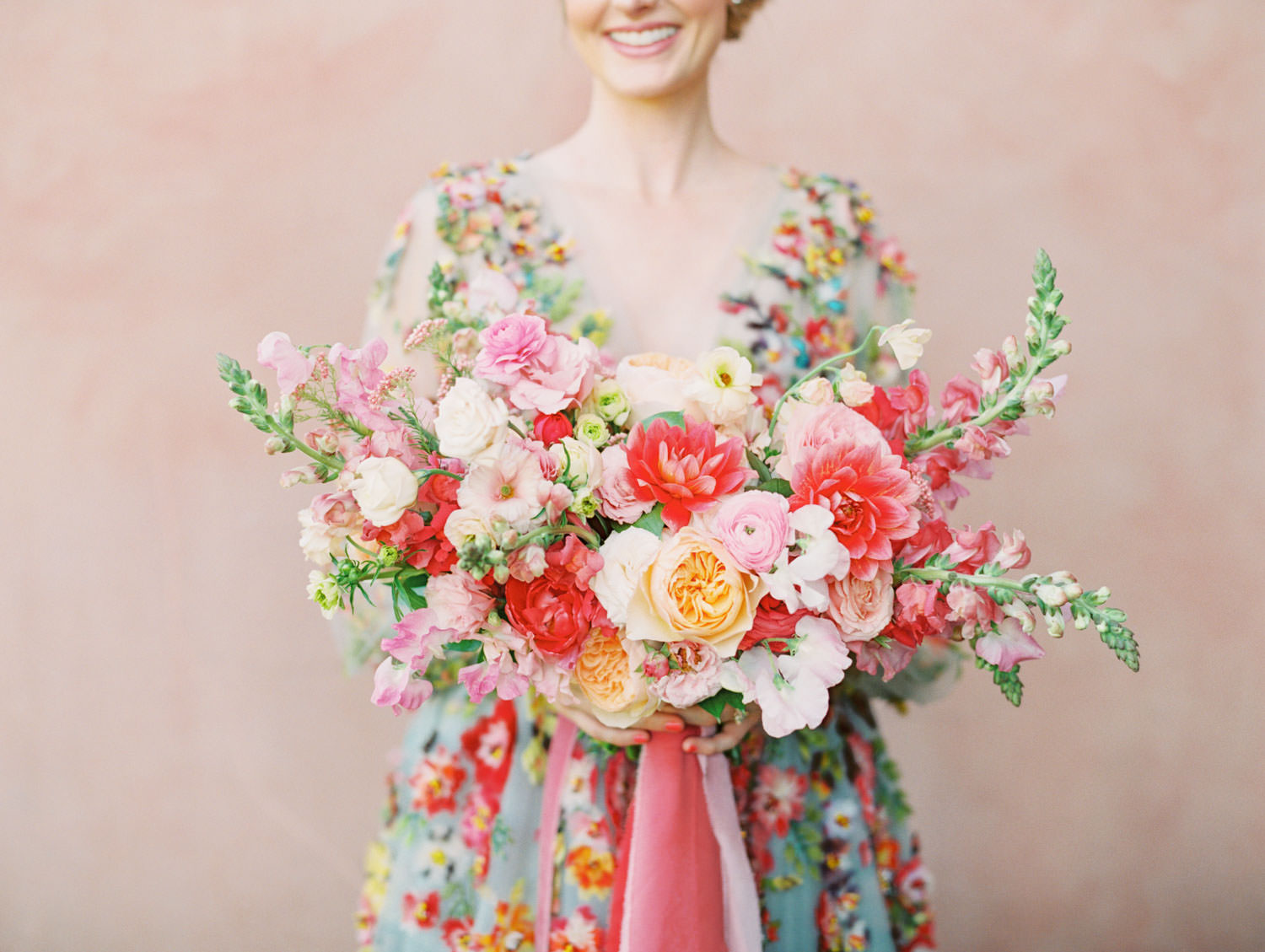Bride wearing a Marchesa blue and pink floral long sleeve couture gown with floral appliques. Large bridal bouquet of mostly pink tones roses, peonies, ranunculus, and sweet peas with long bright pink and blush and mauve silk ribbons. Fairmont Grand del Mar wedding published on Martha Stewart Weddings