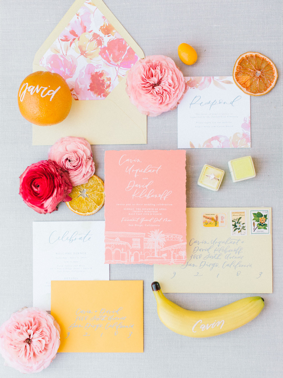 Colorful wedding invitations.. Coral wedding invitation with venue sketch illustration in white ink, soft yellow envelope with pink floral envelope liner, and calligraphy fruit for escort cards. Fairmont Grand del Mar wedding published on Martha Stewart Weddings
