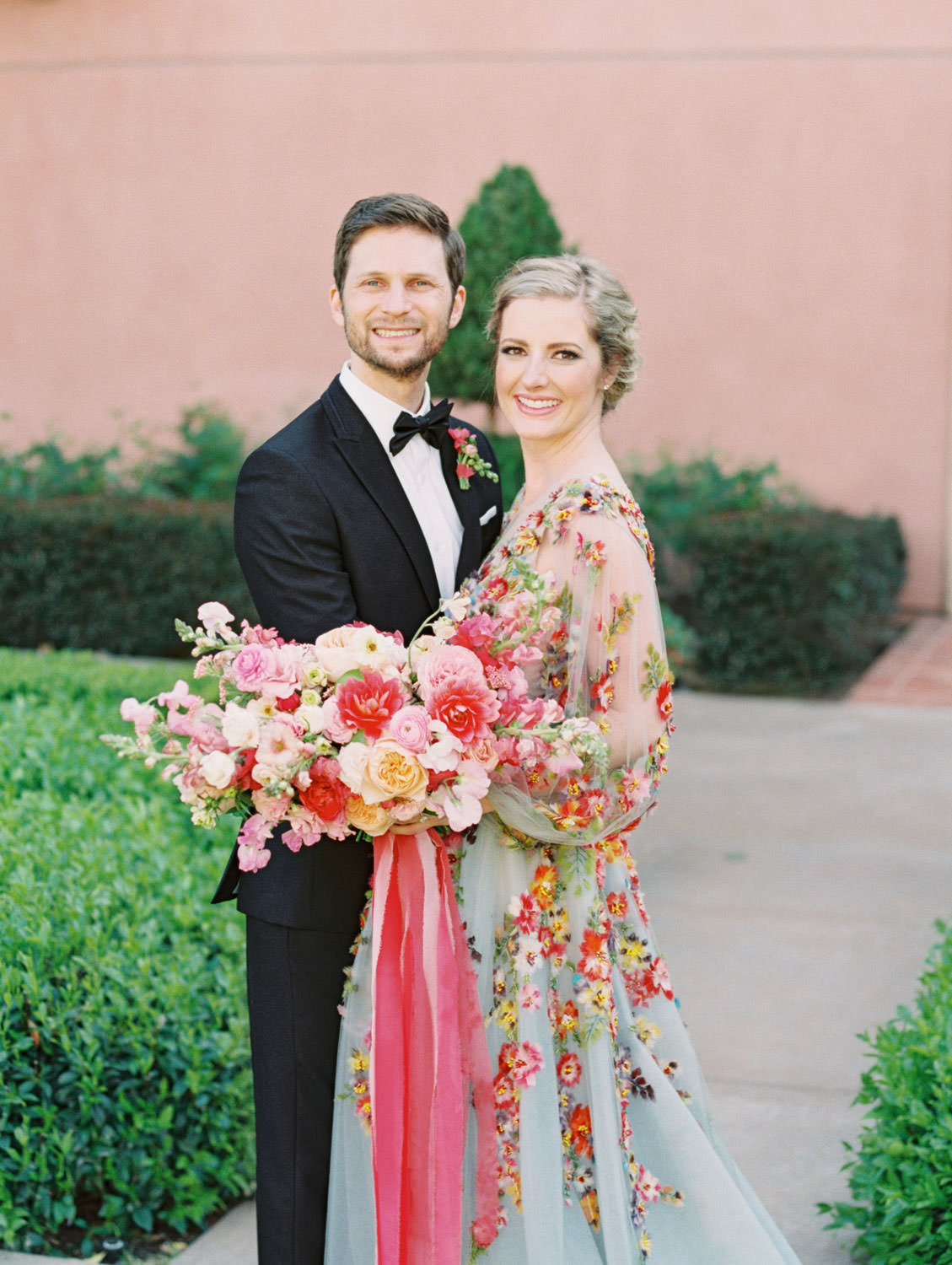 Groom in a black tux smiling at Bride wearing a Marchesa blue and pink floral long sleeve couture gown with floral appliques. Large bridal bouquet of mostly pink tones roses, peonies, ranunculus, and sweet peas with long bright pink and blush and mauve silk ribbons. Fairmont Grand del Mar wedding published on Martha Stewart Weddings