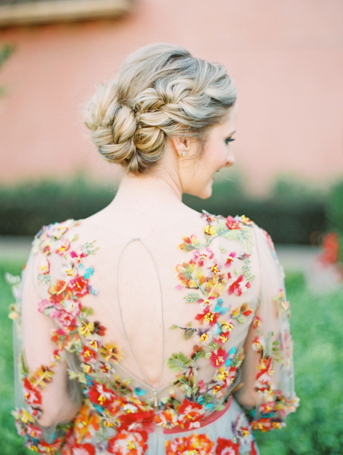 Bride's dutch braid updo for a non-traditional non-bridal wedding day look. Bride wearing a Marchesa blue and pink floral long sleeve couture gown with floral appliques. Fairmont Grand del Mar wedding published on Martha Stewart Weddings