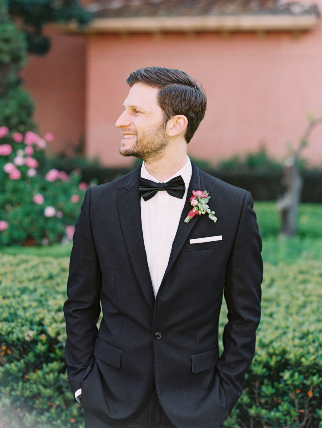 Groom in a black tuxedo with a pink and green boutonniere with a tiny succulent. Fairmont Grand del Mar wedding published on Martha Stewart Weddings