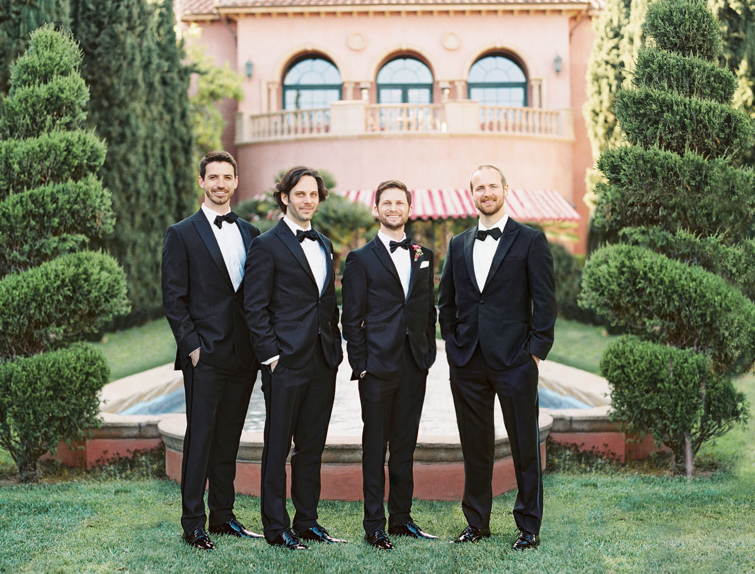 Groom and groomsmen in black tuxedos on the Aria Lawn for bridal party portraits. Fairmont Grand del Mar wedding published on Martha Stewart Weddings