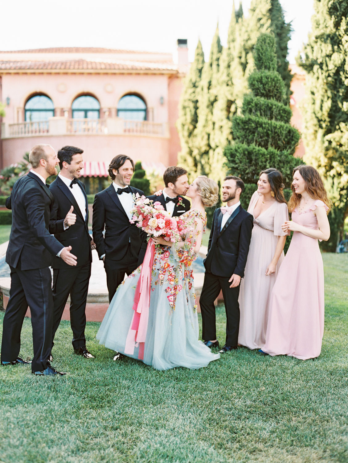 Groom and groomsmen in black tuxedos with bridesmaids in mix match pink gowns and Groom in a black tux walking with bride wearing a colorful Marchesa blue and pink floral long sleeve couture gown with floral appliques on the Aria Lawn for bridal party portraits. Fairmont Grand del Mar wedding published on Martha Stewart Weddings