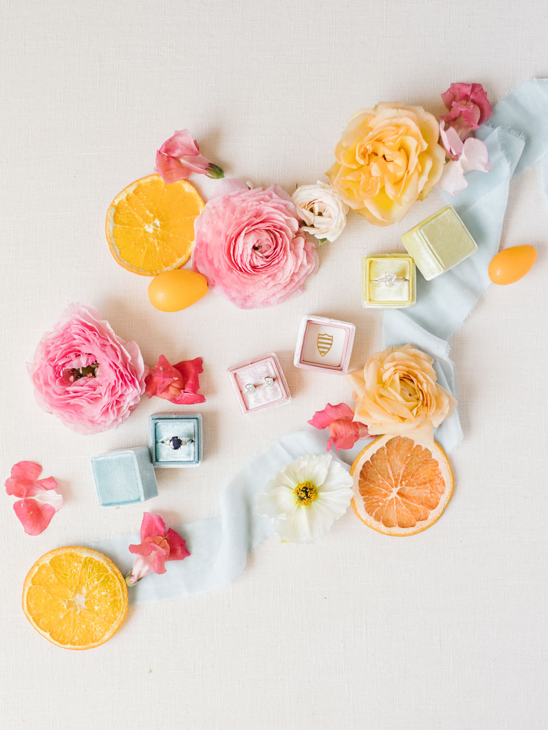Yellow, pink, and blue Mrs Boxes with bride's rings and earrings styled with blue ribbon, dried fruits, and fresh pink flowers. Fairmont Grand del Mar wedding published on Martha Stewart Weddings