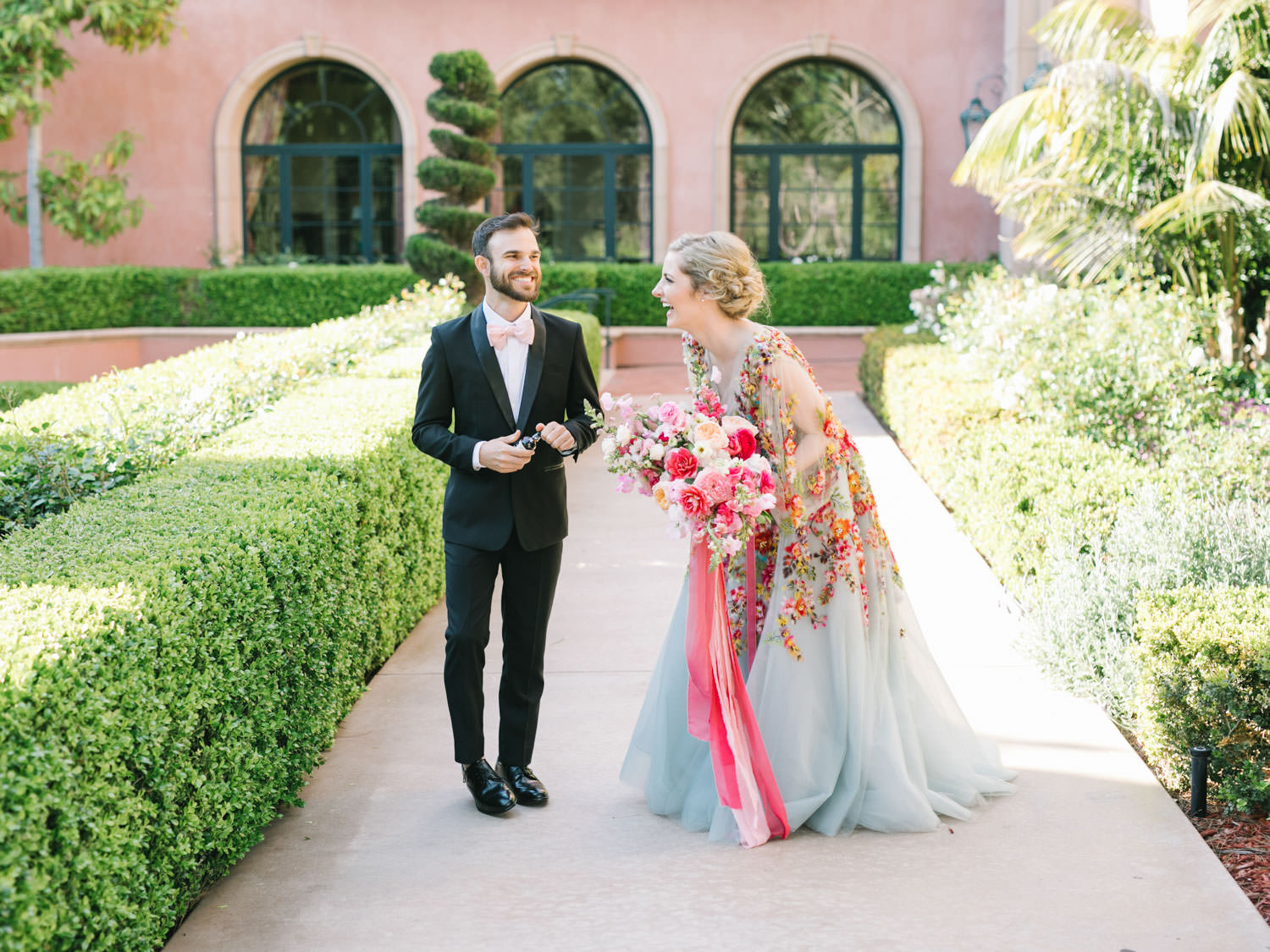 Bridesman in blush bowtie and black tux with Bride wearing a Marchesa blue and pink floral long sleeve couture gown with floral appliques. Large bridal bouquet of mostly pink tones roses, peonies, ranunculus, and sweet peas with long bright pink and blush and mauve silk ribbons. Fairmont Grand del Mar wedding published on Martha Stewart Weddings