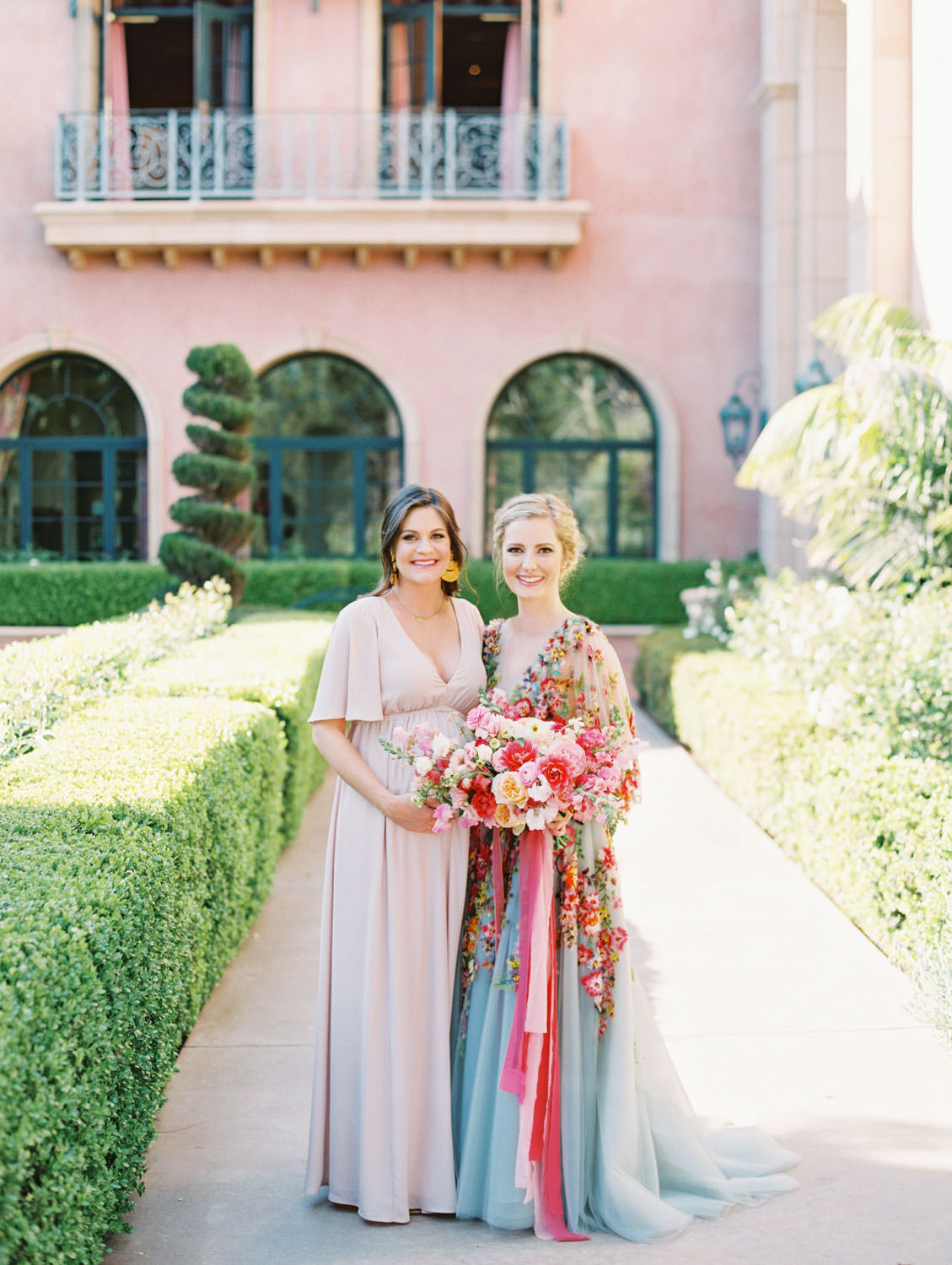 Bridesmaid in blush dress with Bride wearing a Marchesa blue and pink floral long sleeve couture gown with floral appliques. Large bridal bouquet of mostly pink tones roses, peonies, ranunculus, and sweet peas with long bright pink and blush and mauve silk ribbons. Fairmont Grand del Mar wedding published on Martha Stewart Weddings