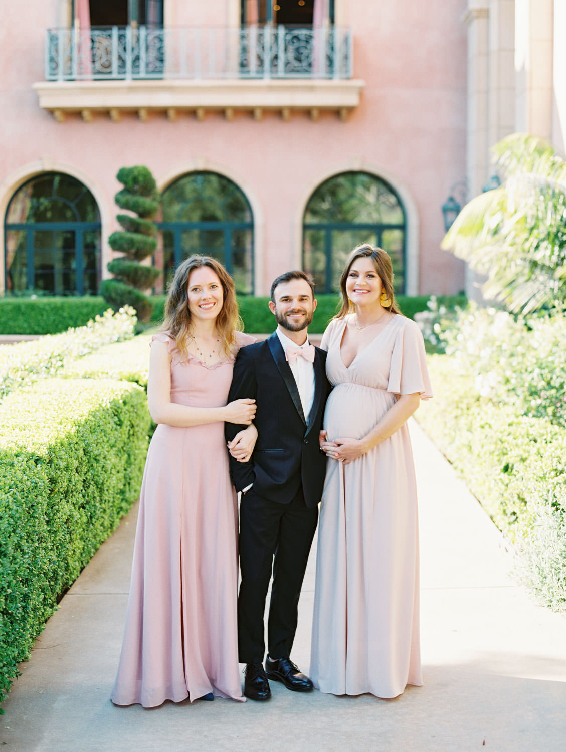 Bridesmaids in mix match pink dresses with bridesman in black tux and pink bowtie. Fairmont Grand del Mar wedding published on Martha Stewart Weddings