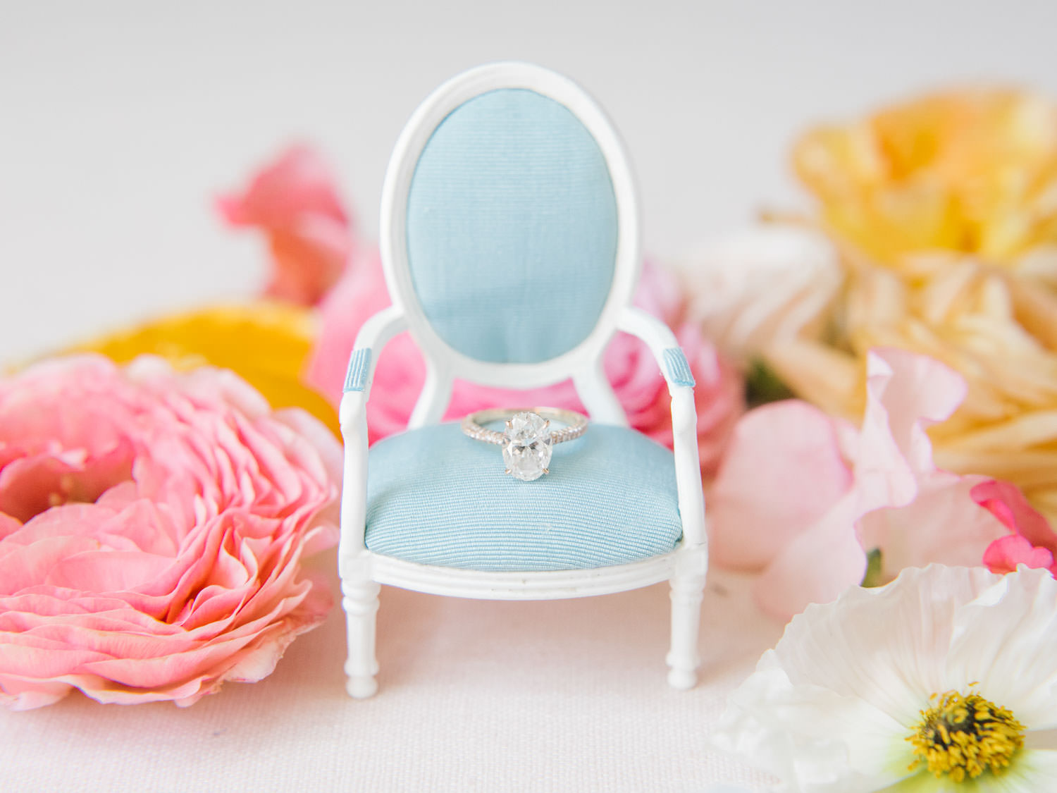 Bride's oval engagement ring on a miniature blue oak louis armchair styled with dried fruits, and fresh pink flowers. Fairmont Grand del Mar wedding published on Martha Stewart Weddings