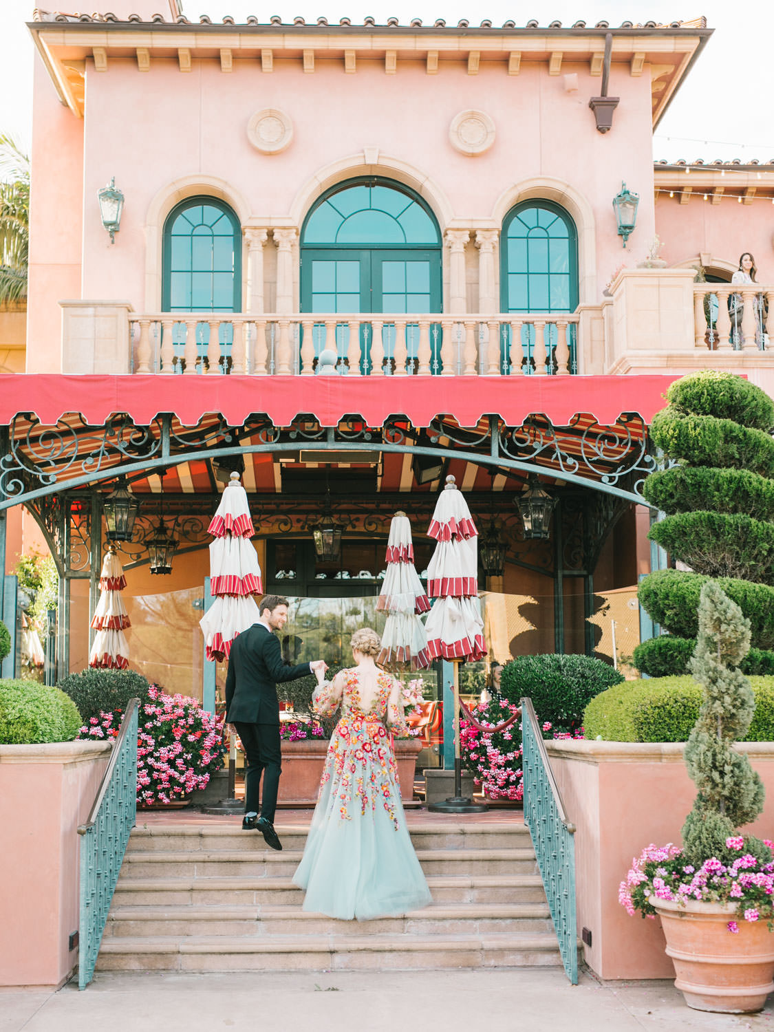 Groom in a black tux walking up grand staircase with bride wearing a colorful Marchesa blue and pink floral long sleeve couture gown with floral appliques. Fairmont Grand del Mar wedding published on Martha Stewart Weddings