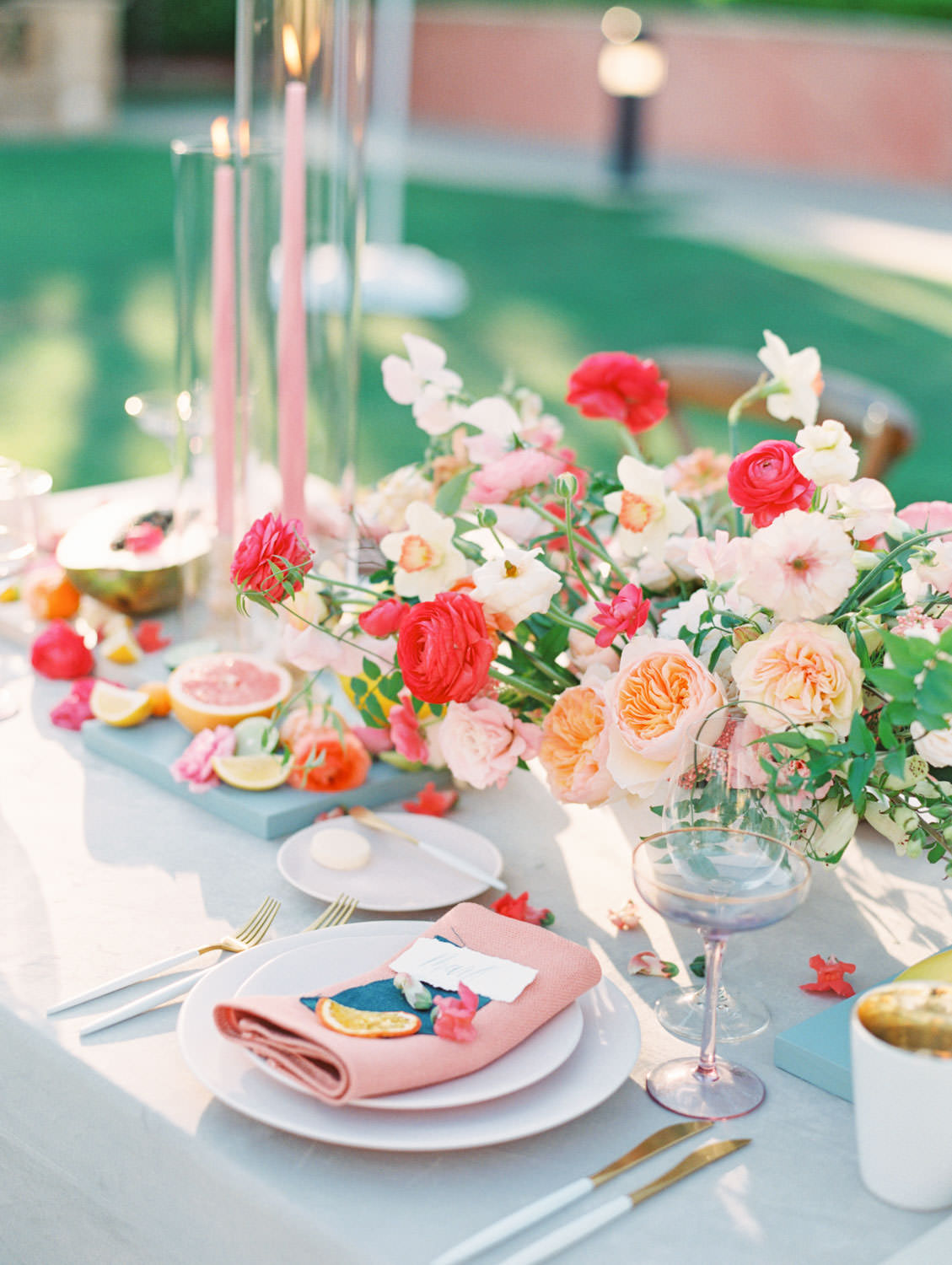Al fresco reception with table covered in blue velvet linen. Soft blush plates, coral napkin with turquoise cloth square on top and hand torn calligraphy place card. Gold flatware with white handles, pink taper candles in hurricanes, and centerpiece with ivory, peach, pink, yellow, and green roses, ranunculus, daffodils, sweet peas, and peonies. A Wedding Photographer's Fairmont Grand Del Mar Wedding
