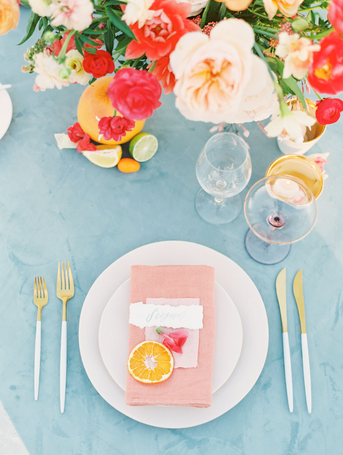 Al fresco reception with table covered in blue velvet linen. Soft blush plates, coral napkin with turquoise cloth square on top and hand torn calligraphy place card. Gold flatware with white handles, pink taper candles in hurricanes, and centerpiece with ivory, peach, pink, yellow, and green roses, ranunculus, daffodils, sweet peas, and peonies.. A Wedding Photographer's Fairmont Grand Del Mar Wedding