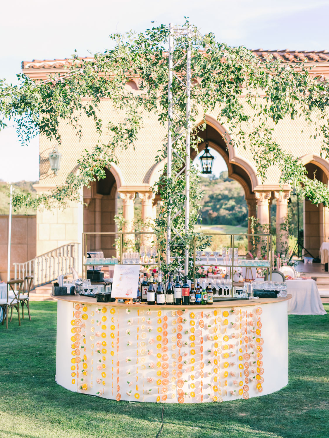 Round circular bar with wagon wheel market lighting covered in greenery smilax. Hanging dried fruit from the bar. A Wedding Photographer's Fairmont Grand Del Mar Wedding
