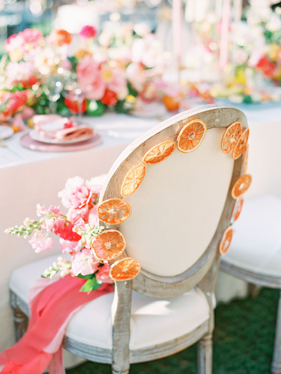 Al fresco reception with table covered in ivory velvet linen. Oak louis chair with dried fruit decorated and hung on the back of the chair. Mauve charger, soft blush plates, coral napkin with grey cloth square on top and hand torn calligraphy place card. Gold flatware with white handles, pink taper candles in hurricanes, and centerpiece with ivory, peach, pink, yellow, and green roses, ranunculus, daffodils, sweet peas, and peonies.. A Wedding Photographer's Fairmont Grand Del Mar Wedding