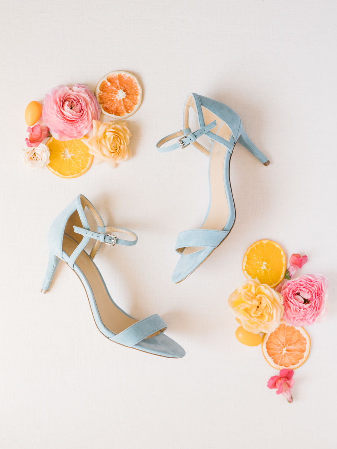 Bride's french blue velvet heels from Michael Kors styled with dried fruits, and fresh pink flowers. Fairmont Grand del Mar wedding published on Martha Stewart Weddings