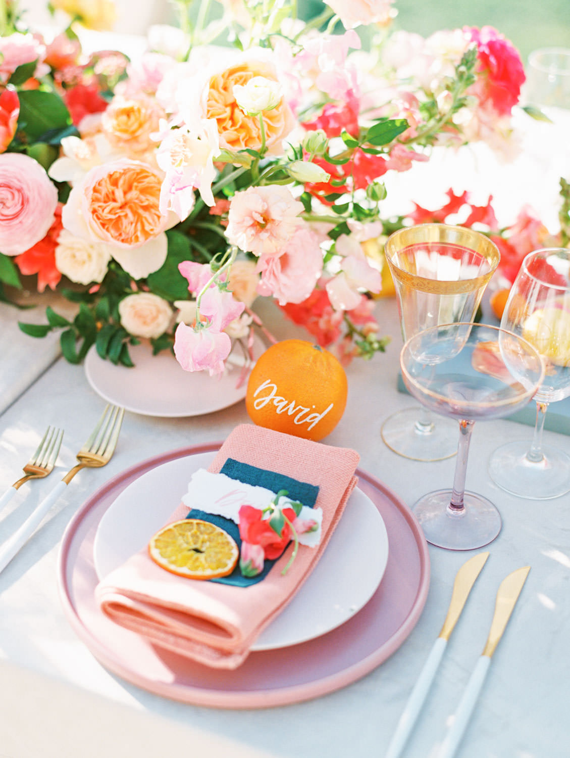 Al fresco reception with table covered in ivory velvet linen. Orange fruit escort card. Mauve charger, soft blush plates, coral napkin with grey cloth square on top and hand torn calligraphy place card. Gold flatware with white handles, pink taper candles in hurricanes, and centerpiece with ivory, peach, pink, yellow, and green roses, ranunculus, daffodils, sweet peas, and peonies.. A Wedding Photographer's Fairmont Grand Del Mar Wedding