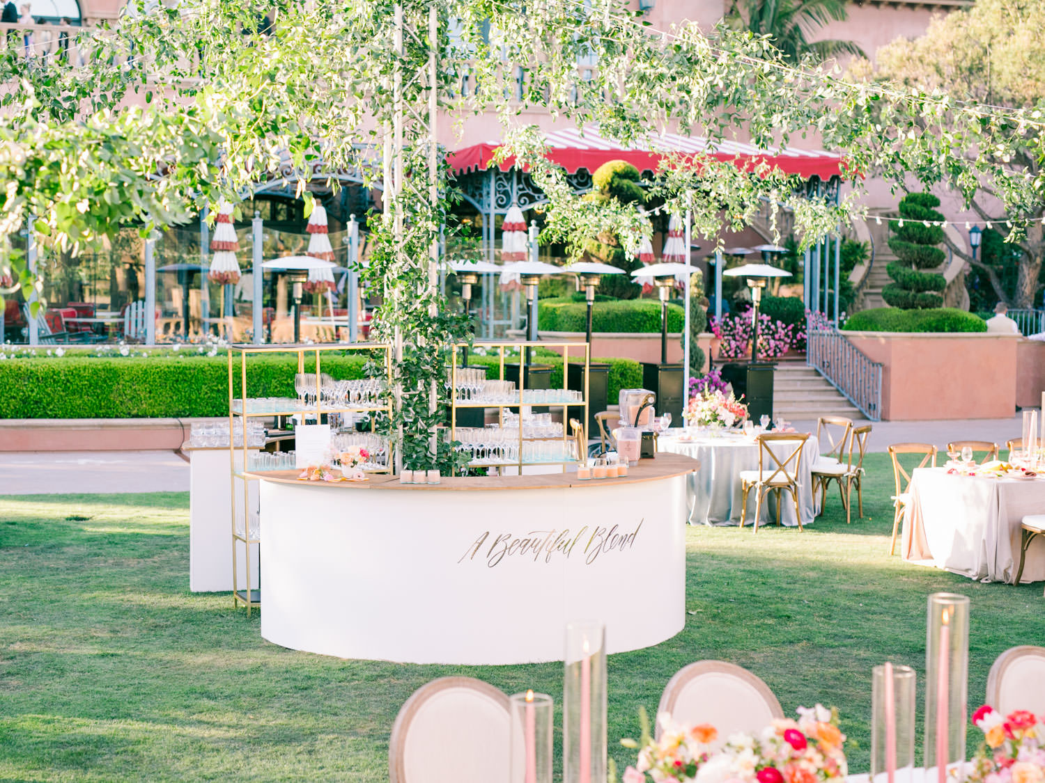 Round circular bar with wagon wheel market lighting covered in greenery smilax. Acrylic laser cut smoothie bar sign. A Wedding Photographer's Fairmont Grand Del Mar Wedding