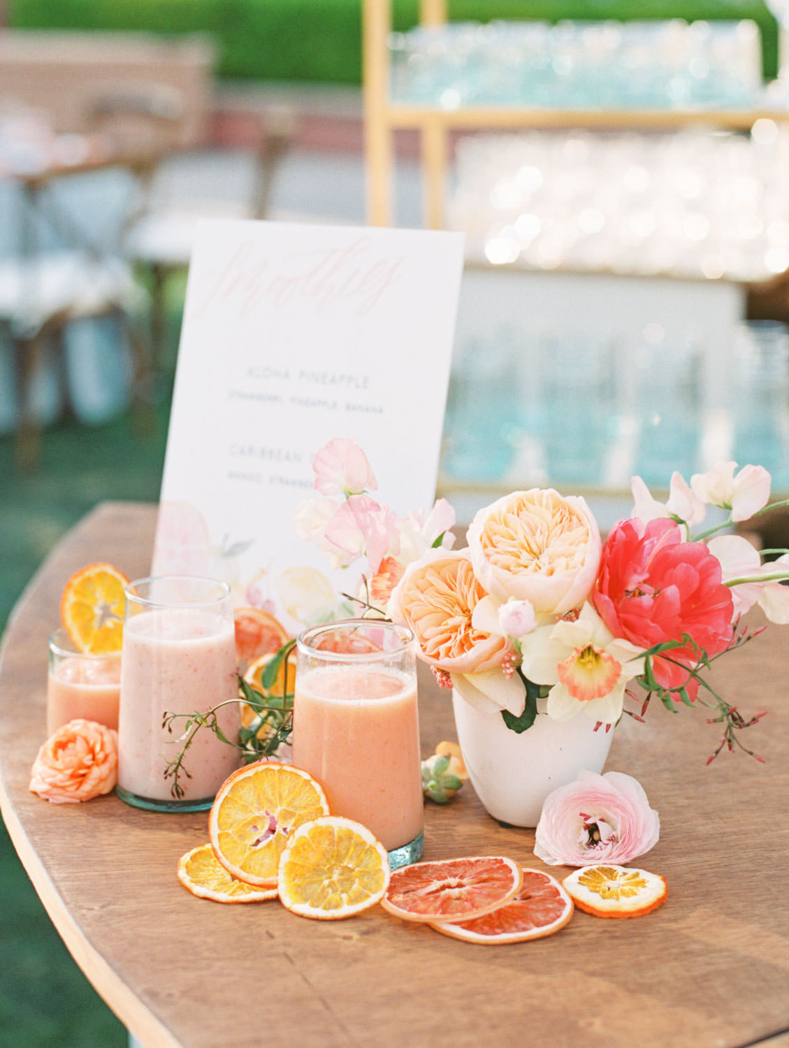 Smoothie bar from Jamba Juice for a wedding. Smoothies styled with dried fruit and flowers of peonies, roses, and sweet peas in pink, orange, peach, and fuschia. A Wedding Photographer's Fairmont Grand Del Mar Wedding