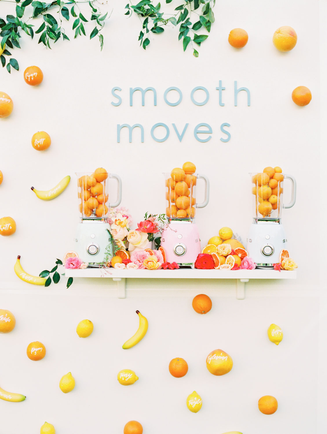 "Outdoor escort display with text ""smooth moves"" and smilax framing top. Escort cards made from faux fruit bananas and oranges with guest names in white ink. Three colorful Smeg blenders on a shelf filled with fruit. A Wedding Photographer's Fairmont Grand Del Mar Wedding"