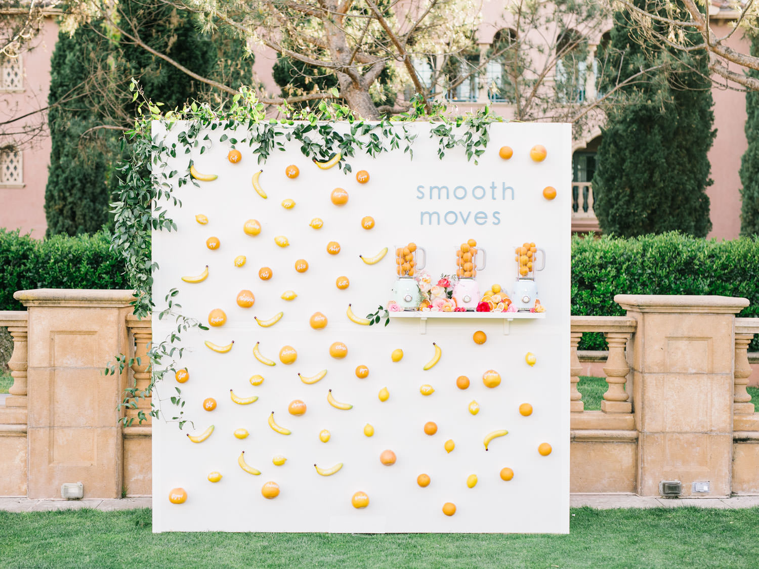"Outdoor escort display with text ""smooth moves"" and smilax framing top and side. Escort cards made from faux fruit bananas and oranges with guest names in white ink. Three colorful Smeg blenders on a shelf filled with fruit. A Wedding Photographer's Fairmont Grand Del Mar Wedding"
