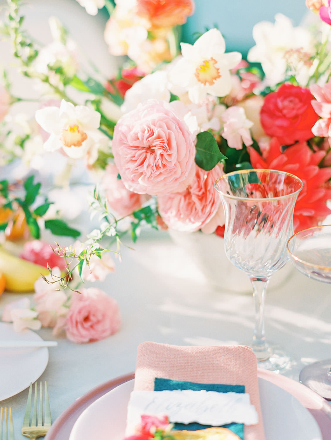 Al fresco reception with table covered in ivory velvet linen. Banana escort card. Mauve charger, soft blush plates, coral napkin with grey cloth square on top and hand torn calligraphy place card. Gold flatware with white handles, pink taper candles in hurricanes, and centerpiece with ivory, peach, pink, yellow, and green roses, ranunculus, daffodils, sweet peas, and peonies.. A Wedding Photographer's Fairmont Grand Del Mar Wedding