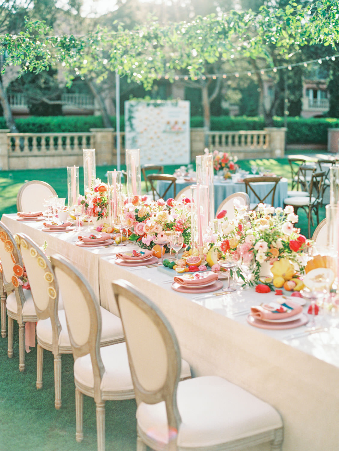 Al fresco reception with table covered in ivory velvet linen. Oak louis chairs. Smilax hanging on market lights above the table. Mauve charger, soft blush plates, coral napkin with grey cloth square on top and hand torn calligraphy place card. Gold flatware with white handles, pink taper candles in hurricanes, and centerpiece with ivory, peach, pink, yellow, and green roses, ranunculus, daffodils, sweet peas, and peonies. A Wedding Photographer's Fairmont Grand Del Mar Wedding
