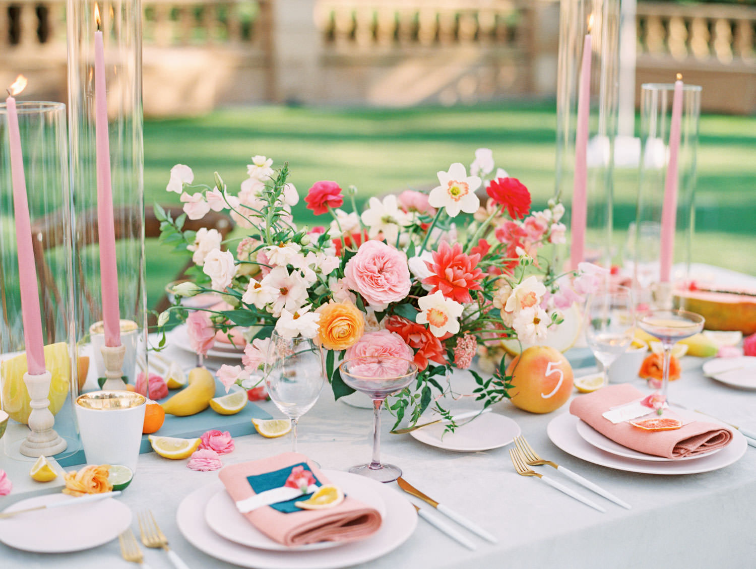 Al fresco reception with table covered in ivory bone velvet linen. Banana escort card. Mauve charger, soft blush plates, coral napkin with grey cloth square on top and hand torn calligraphy place card. Gold flatware with white handles, pink taper candles in hurricanes, and centerpiece with ivory, peach, pink, yellow, and green roses, ranunculus, daffodils, sweet peas, and peonies. A Wedding Photographer's Fairmont Grand Del Mar Wedding