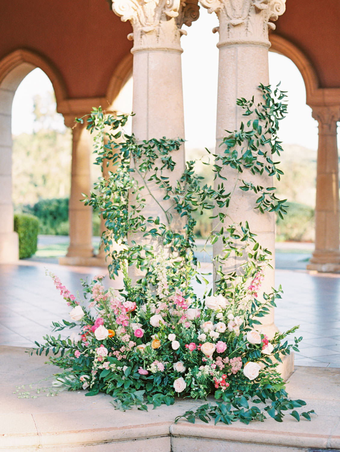 Venue pavilion stage with columns covered in climbing smilax with arrangement at the bottom consisting of roses, ranunculus, daffodils, peonies, and sweet peas. A Wedding Photographer's Fairmont Grand Del Mar Wedding
