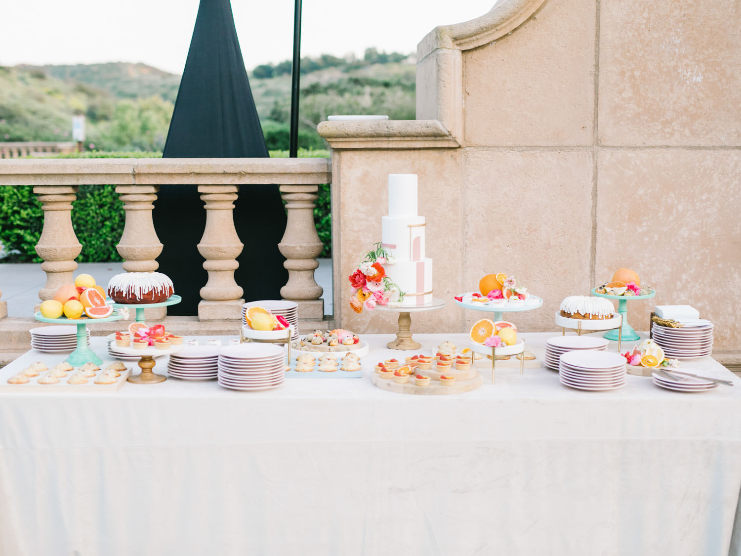 Dessert display with bone velvet linen. Blush plates for serving. Three tier white cake with pink lines for a geometric cake. Cut fruit and flowers styled with desserts.