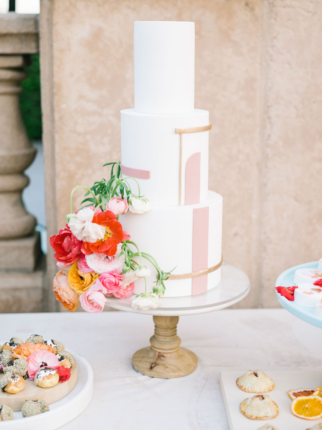 Dessert display with bone velvet linen. Three tier white cake with pink and gold lines for a geometric cake. Cut fruit and flowers styled with desserts.